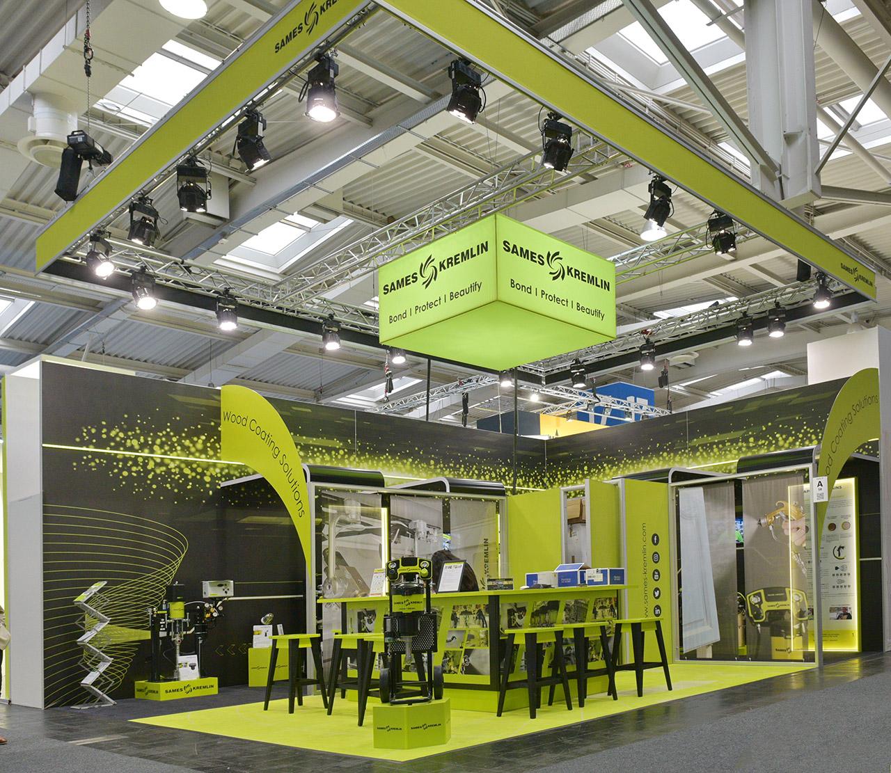 Messebau Düsseldorf: Messestand mit guter Beleuchtung, Logowürfel, Bartheke und Podest für Exponate