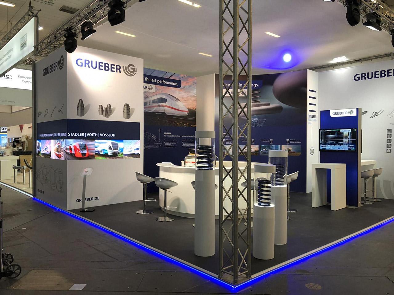 Messestand mit Doppelboden beleuchtet, runde Empfangstheke, Barhocker, Kabine und Grafikelemente - Messebauer Düsseldorf