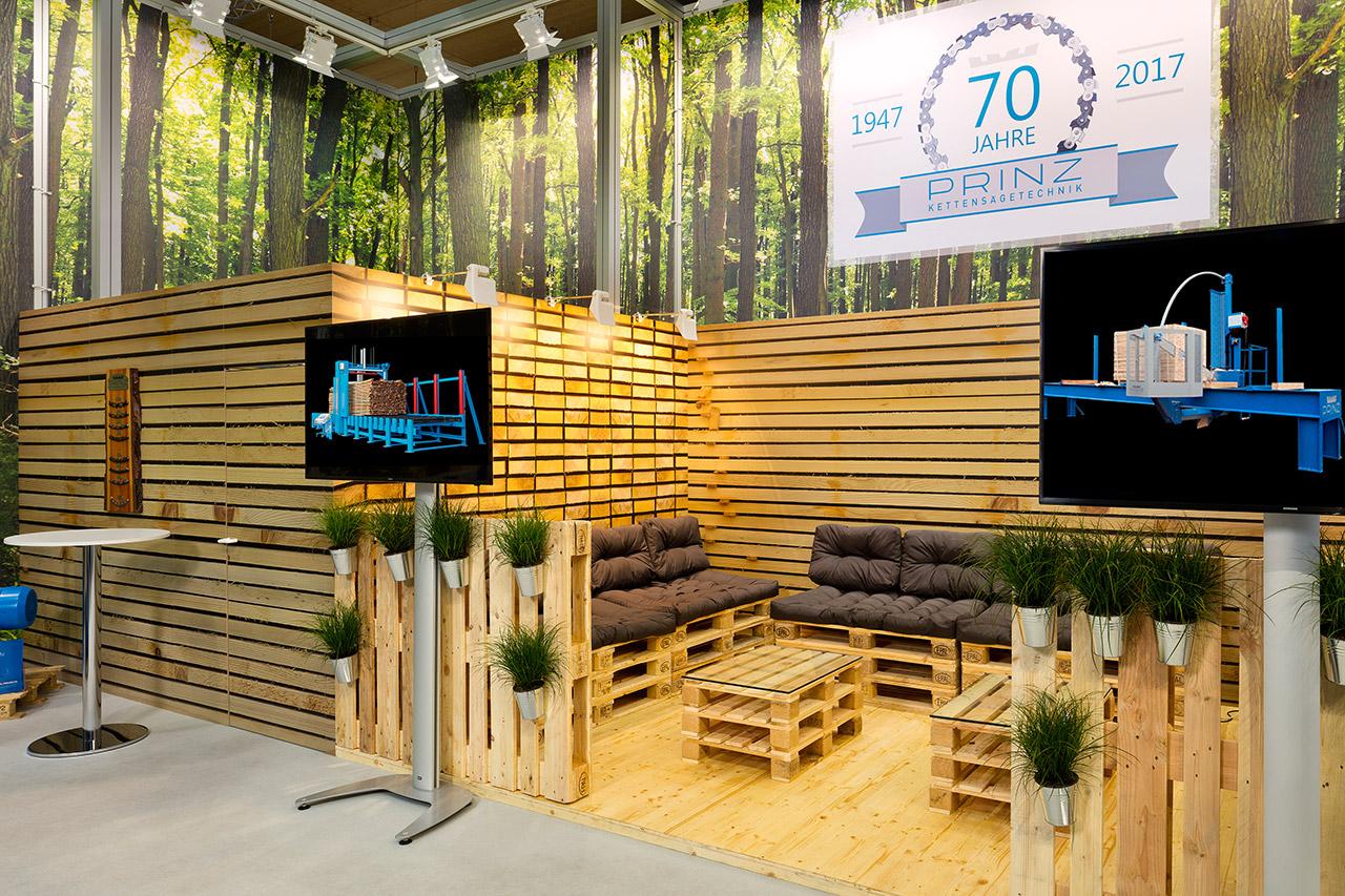 Messebau konventionell: Individueller Messestand mit Holz, Meetingbereich mit Holzpaletten zum Sitzen, Kabine und LED Bildschirme