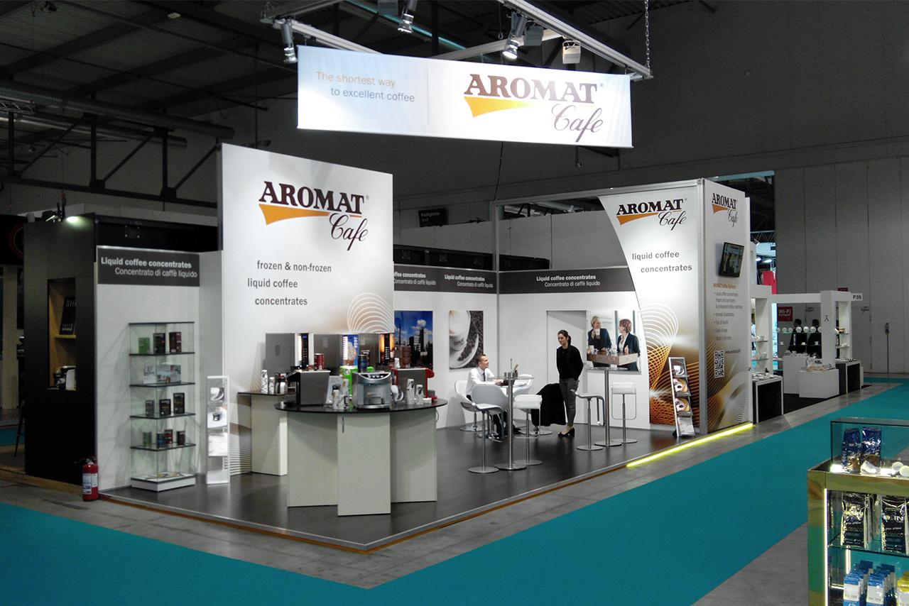 Messestand mit Produktevitrinen, Kaffeeautomaten, Stehtischen auf einem Laminatboden mit Logo-Abhängung - Messebau Köln